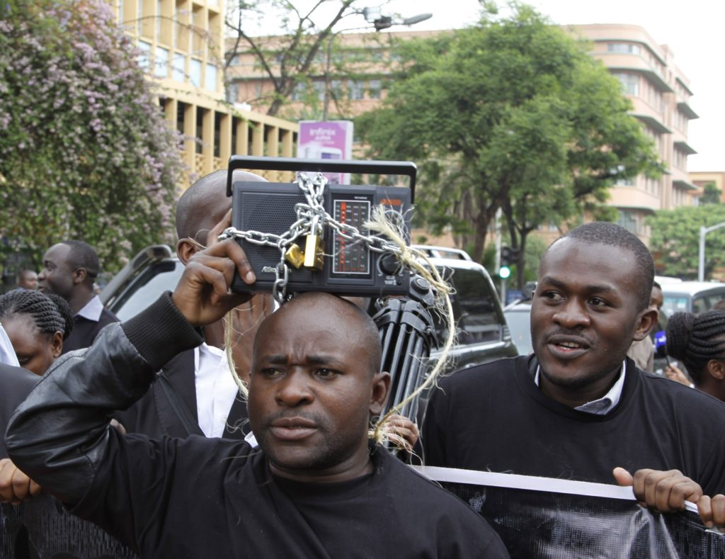 Kenyan journalists display a symbolically locked radio, during a protest against the Media Bill in Nairobi, Kenya, Tuesday, Dec. 3, 2013. A media protest was called on by various media houses to protest new draconian laws that are being tabled by parliament. (AP Photo/Khalil Senosi)